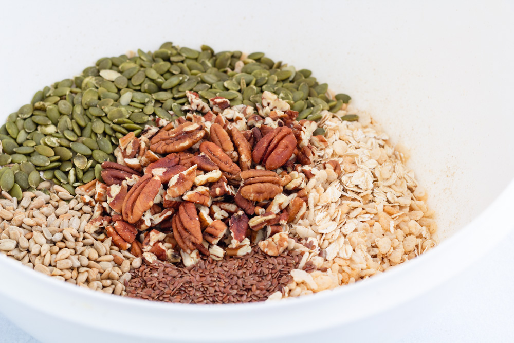 A big bowl holding the dry ingredients; oats, crispy rice cereal, pepitas, sunflower seeds, flaxseeds, and pecans