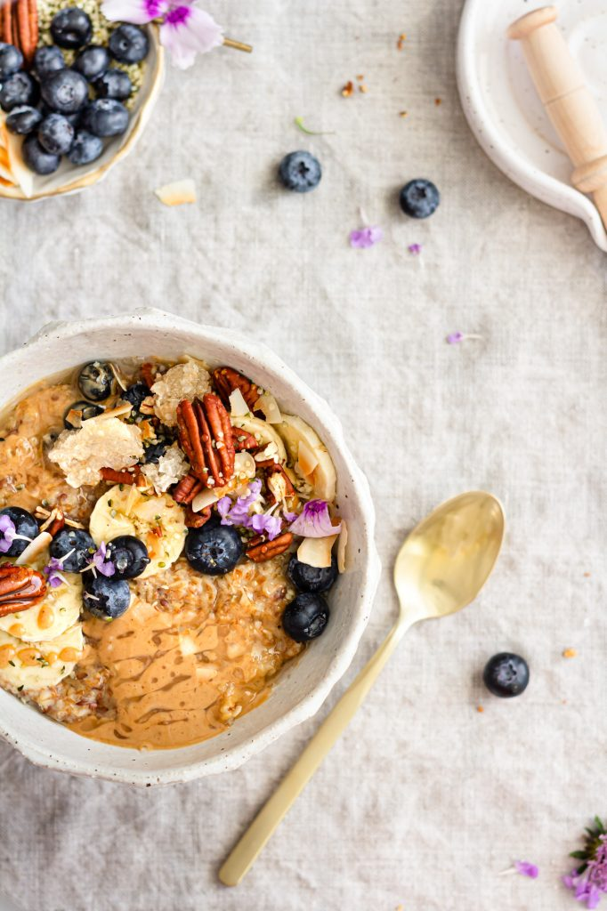 An overhead shot of a delicious looking bowl of oatmeal, peanut butter and honey are melting on the surface.  The dish is topped with slice bananas, blueberries, toasted pecans, large flake coconut, melty honeycomb, hemp seeds, and bright, little, purple flowers.  There is a gold spoon beside the bowl.