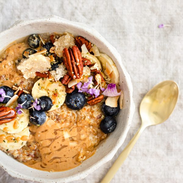 An overhead shot of a hearty and beautiful bowl of oatmeal on a linen cloth. The bowl is dabbed with melted peanut butter, topped with bananas, blueberries, pecans, toasted coconut, honeycomb, hemp seeds, and light purple flowers. All the ingredients have been drizzled with warm honey. It looks ooey gooey good! There is a gold spoon beside the bowl making the oatmeal experience pretty and decadent. There are a few blueberries and flower petals scattered on the table and a spurtle in a spoon rest. Mmmmmmmmmmmmm…..
