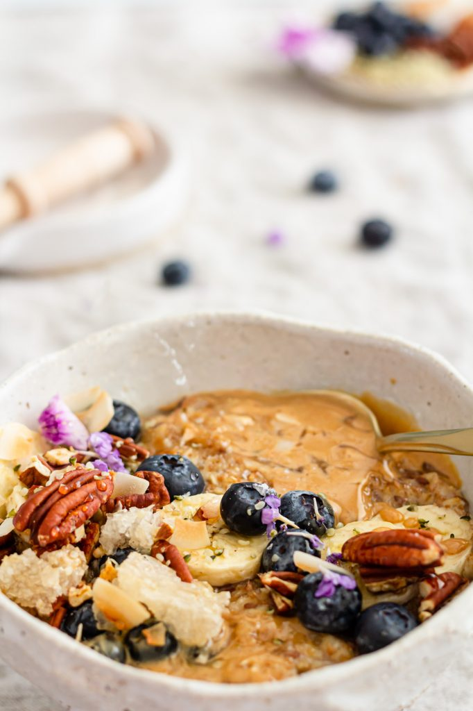 A close-up shot of a delicious looking bowl of oatmeal, peanut butter and honey are melting on the surface.  The dish is topped with slice bananas, blueberries, toasted pecans, large flake coconut, melty honeycomb, hemp seeds, and bright, little, purple flowers.  There is a gold spoon in the bowl.  Mmmmm....