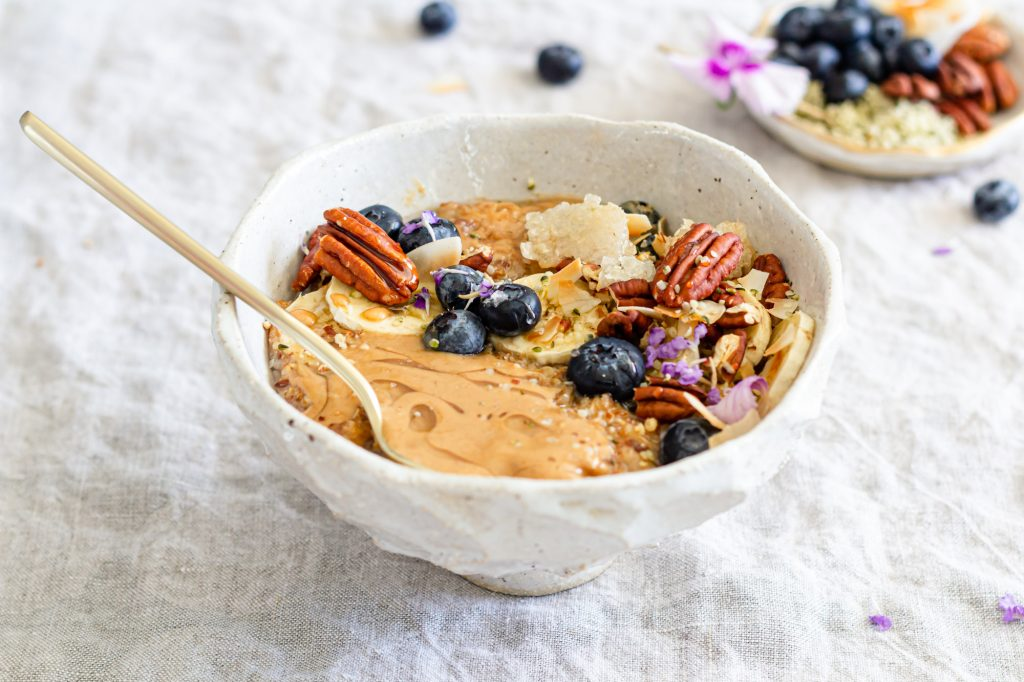 A side shot of a delicious looking bowl of oatmeal, peanut butter and honey are melting on the surface.  The dish is topped with slice bananas, blueberries, toasted pecans, large flake coconut, melty honeycomb, hemp seeds, and bright, little, purple flowers.  There is a gold spoon in the bowl.