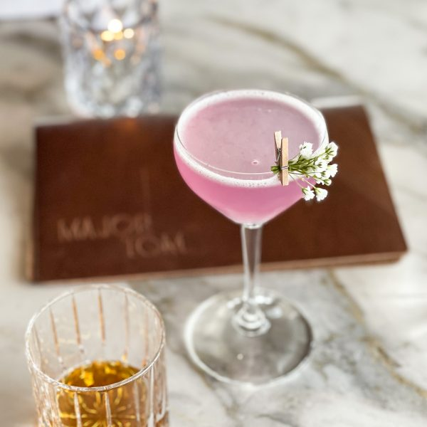 A dainty cocktail glass with a berry pink drink, foam around the rim, a sprig of baby's breath clipped to the rim with a tiny clothespin. An ounce of bourbon in an etched crystal rocks glass. The Major Tom cocktail menu bound in leather. A candle glows on a taupe marble tabletop.