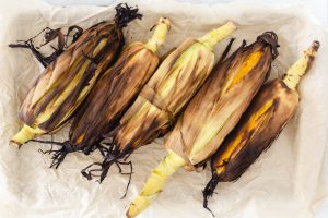 Grilled corn on the cob still in the husk