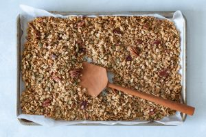 A tray of freshly baked granola with a wooden spoon