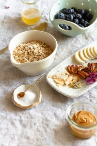 Ingredients for the peanut butter and honey oatmeal are placed on a beige linen cloth. Oats in a bowl is predominant in the centre, blueberries have been washed in a berry bowl. There is liquid honey in a reused Riviera yogurt jar; peanut butter in a little Weck jar; toasted pecans and coconut, hemp seeds, and purple flowers on a rectangular plate; salt and cinnamon are on a little plate in the background. A gold spoon invites you to want to dig in.