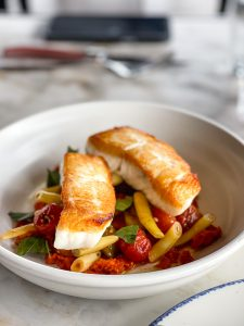 Two filets of halibut, both snowy white and golden yellow lay on a bed of sweet tomatoes, yellow beans and basil.
