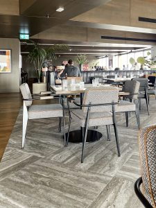 Driftwood gray checkerboard flooring grounds the more modern than midcentury chairs. They sport black frames with tweed fabric and caramel leather piping.